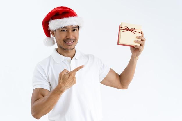Szczęśliwy mężczyzna jest ubranym santa kapelusz i wskazuje przy prezenta pudełkiem