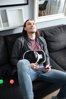 Szczęśliwy mężczyzna kłama na kanapie w domu trzyma 3d szkła