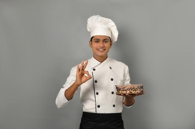 Szczęśliwy mężczyzna kucharz ubrany w mundur trzymający talerz z czekoladowym ciastem i pokazując gest ok jedną ręką