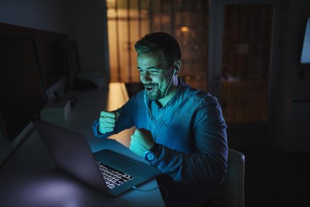 Szczęśliwy mężczyzna ma rozmowę wideo i gestykuluje wygranie podczas gdy siedzący w biurze póżno przy nocą.