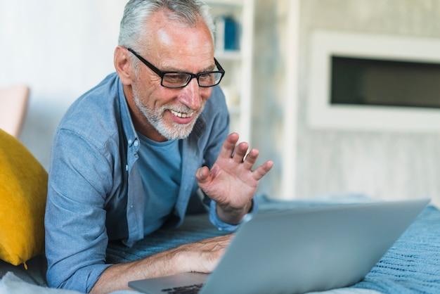 Szczęśliwy mężczyzna macha rękę podczas wideo gawędzi na laptopie w domu
