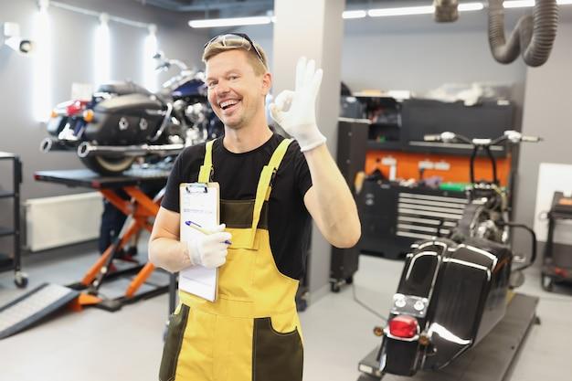 Szczęśliwy mężczyzna mechanik samochodowy wykonuje ok gest w zaleceniach serwisowych i wysokiej jakości