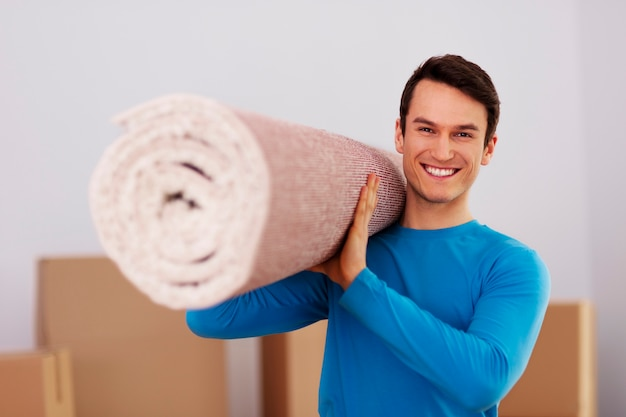 Szczęśliwy mężczyzna niosący dywan w nowym domu