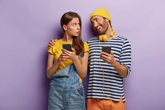 Szczęśliwy mężczyzna obejmuje zmartwioną dziewczynę, uspokaja i przyjemnie rozmawia, używa nowoczesnych telefonów komórkowych, stoi blisko fioletowej ściany