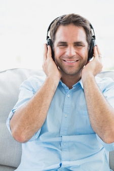 Szczęśliwy mężczyzna obsiadanie na kanapie słucha muzyczny ono uśmiecha się przy kamerą