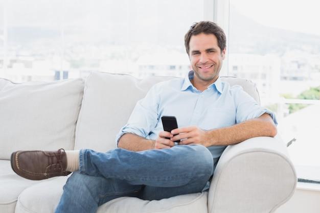 Szczęśliwy mężczyzna obsiadanie na leżance używać jego smartphone
