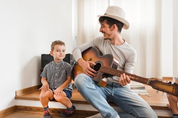 Szczęśliwy mężczyzna obsiadanie z jego synem bawić się gitarę