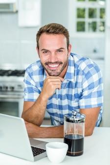 Szczęśliwy mężczyzna opiera laptopem przy stołem w kuchni