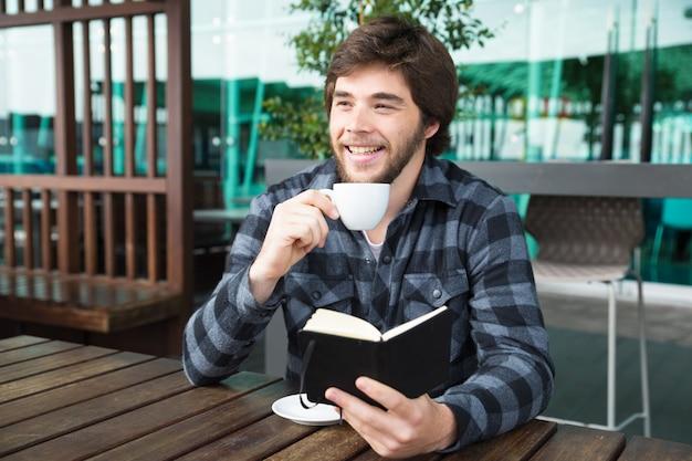 Szczęśliwy mężczyzna pije kawę i czyta dzienniczek w plenerowej kawiarni