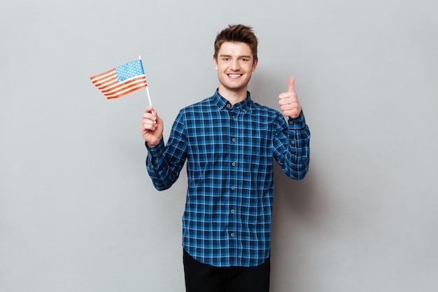 Szczęśliwy mężczyzna pokazuje aprobaty i trzyma usa flaga.