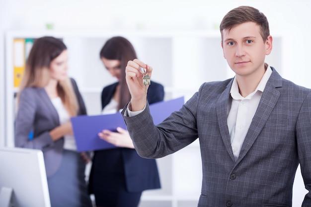 Szczęśliwy mężczyzna pośrednik handlu nieruchomościami pokazuje klucze