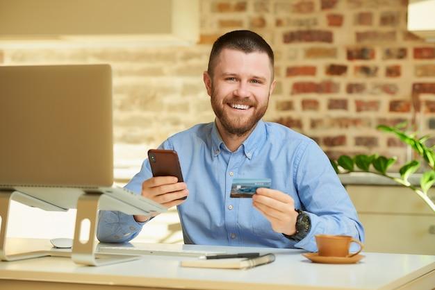 Szczęśliwy mężczyzna pozuje podczas czytania informacji z tyłu karty kredytowej i pisania na smartfonie, aby dokonać zakupu w domu