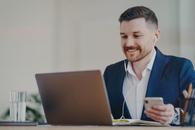Szczęśliwy mężczyzna pracownik biurowy korzysta z nowoczesnych technologii pozuje na biurku trzyma telefon komórkowy prowadzi wideorozmowę przez laptopa nosi słuchawki ubrany formalnie ma zadowoloną ekspresję zegarki biznesowe webinar