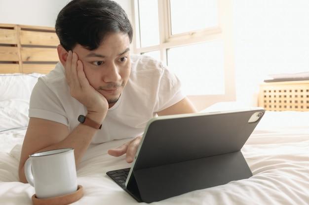 Szczęśliwy mężczyzna pracuje na swoim tablecie z filiżanką kawy na łóżku