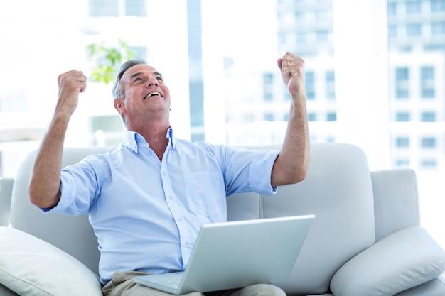 Szczęśliwy mężczyzna przyglądający up podczas gdy pracujący na laptopie