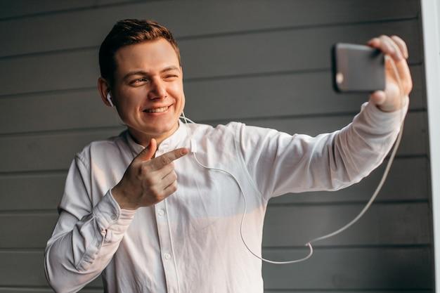 Szczęśliwy mężczyzna robi facetime wideo dzwoni z smartphone w domu, używa zoom spotyka online app, ogólnospołeczny dystansowanie, pracuje zdalnie pojęcie