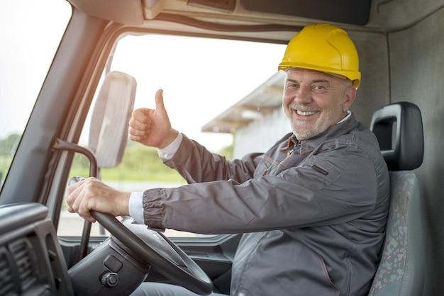 Szczęśliwy mężczyzna robotnik budowlany robi gest kciuka w górę w ciężarówce pod światłem słonecznym