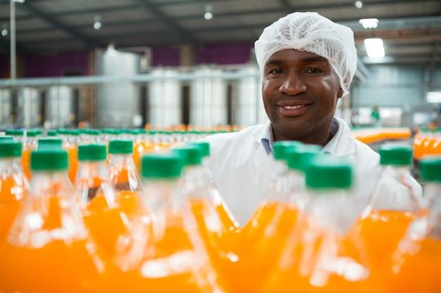 Szczęśliwy mężczyzna robotnik stojący przy butelkach soku pomarańczowego w fabryce