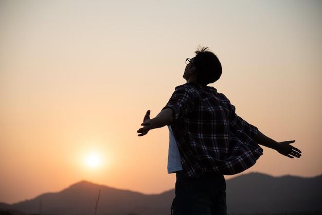 Szczęśliwy mężczyzna rozprzestrzenia ręki, podróżuje styl życia, wolność sukcesu pojęcie.