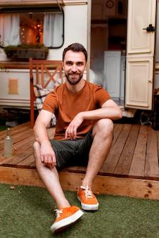 Szczęśliwy mężczyzna siedzi na ganku
