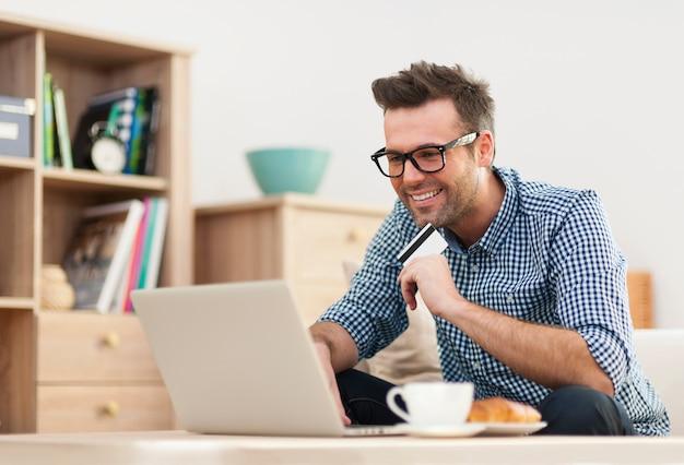 Szczęśliwy mężczyzna siedzi na kanapie z laptopem i kartą kredytową