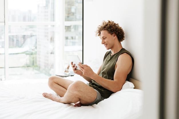 Szczęśliwy mężczyzna siedzi na łóżku w domu przy użyciu komputera typu tablet