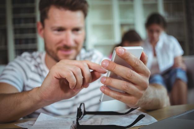 Szczęśliwy mężczyzna siedzi przy stole i używa swojego telefonu komórkowego
