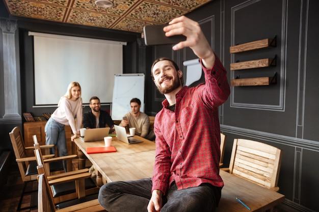 Szczęśliwy mężczyzna siedzi w biurze i zrobić selfie
