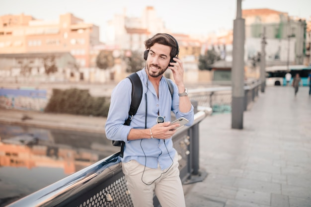 Szczęśliwy mężczyzna słucha muzyka z telefonem komórkowym