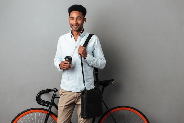 Szczęśliwy mężczyzna stoi blisko bicyklu odizolowywał słuchającą muzykę pije kawę.