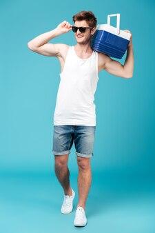 Szczęśliwy mężczyzna stoi nad błękitem odizolowywającym.