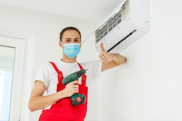 Szczęśliwy mężczyzna technik naprawy klimatyzatora za pomocą śrubokręta