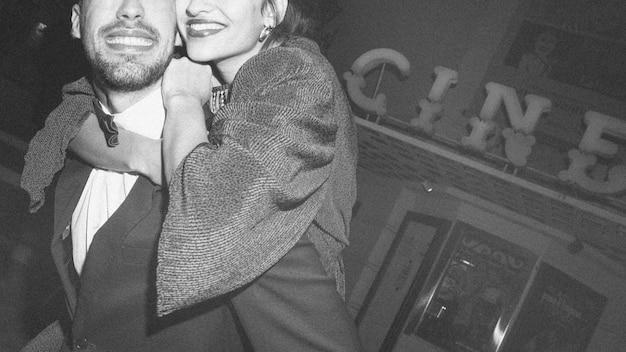 Szczęśliwy mężczyzna trzyma dalej tylną uśmiechniętą kobietę na ulicie