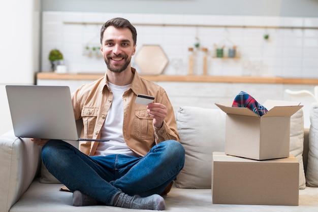 Szczęśliwy mężczyzna trzyma laptop i kredytową kartę