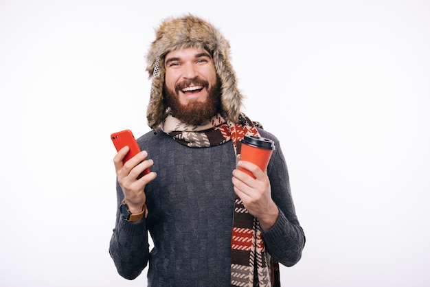 Szczęśliwy mężczyzna trzyma smartphone i filiżankę kawy iść