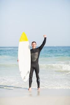 Szczęśliwy mężczyzna trzyma surfboard na plaży