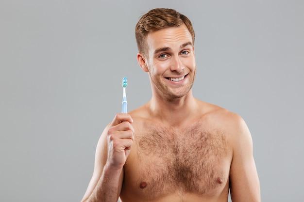 Szczęśliwy mężczyzna trzyma szczoteczkę do zębów na szarej ścianie odizolowanej na szarej ścianie