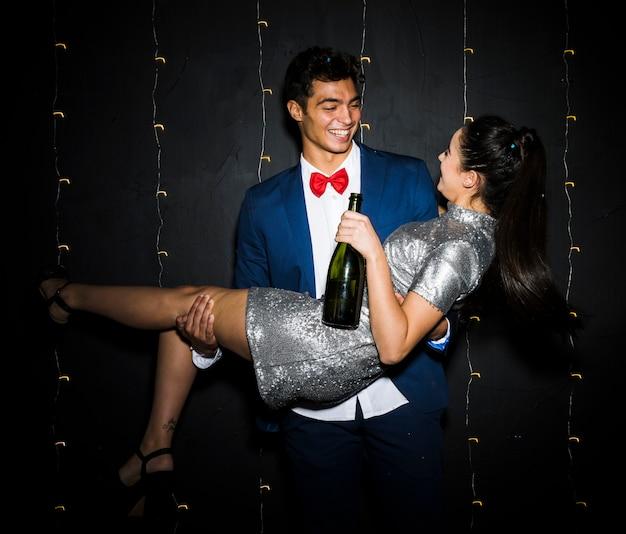 Szczęśliwy mężczyzna trzyma uśmiechniętej kobiety z butelką