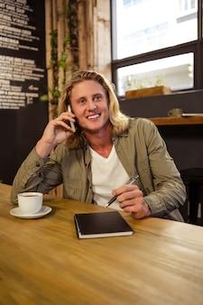 Szczęśliwy mężczyzna używa jego smartphone