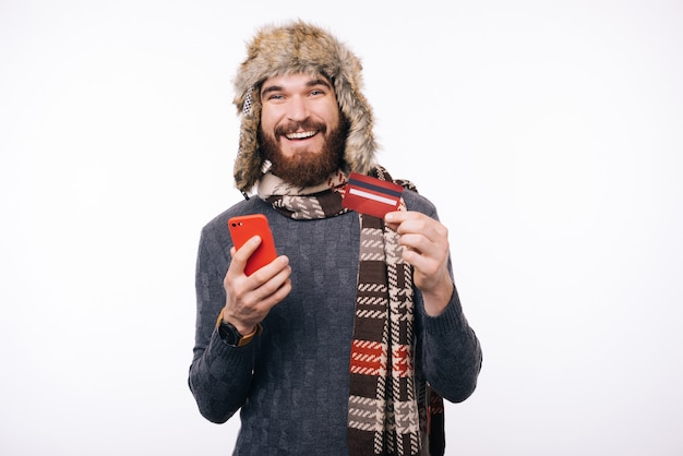 Szczęśliwy mężczyzna używa kredytową kartę i smartphone nad białym tłem
