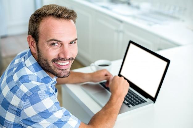 Szczęśliwy mężczyzna używa laptop podczas gdy siedzący przy stołem w kuchni