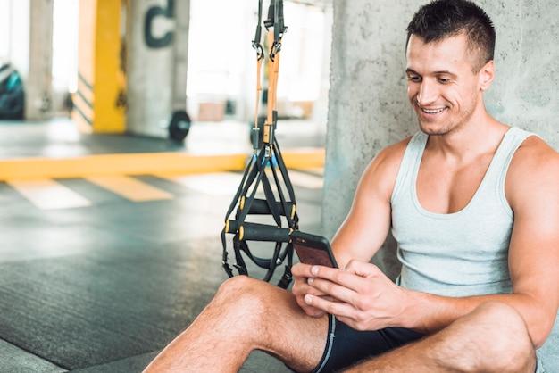 Szczęśliwy mężczyzna używa telefon komórkowego w gym