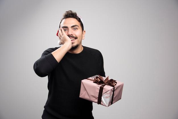 Szczęśliwy mężczyzna w czapce świętego mikołaja trzymający prezent noworoczny.