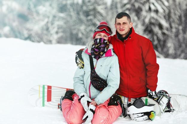 Szczęśliwy mężczyzna w czerwonej narciarskiej kurtce i kobieta w błękicie jeden siedzimy na ich snowboards na halnym wzgórzu