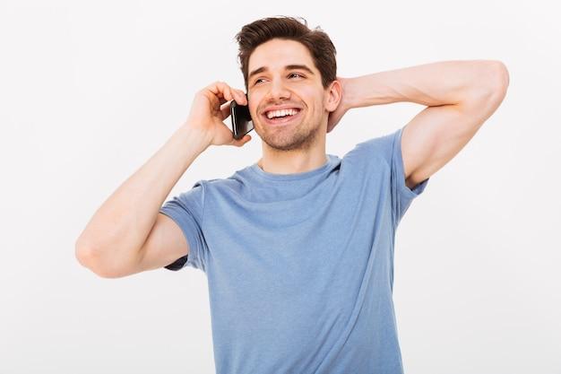 Szczęśliwy mężczyzna w koszulce bierze smartphone podczas gdy trzymający głowę i patrzejący daleko od nad szarości ścianą