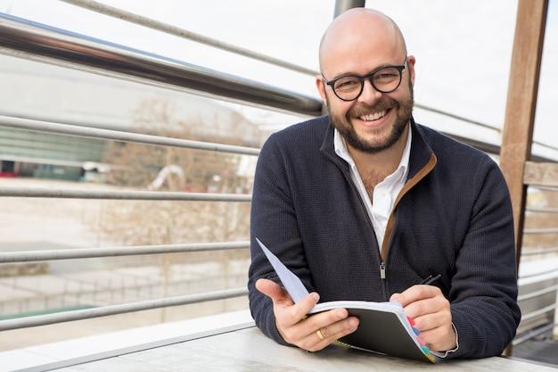 Szczęśliwy mężczyzna w średnim wieku robi notatki w ulicznej kawiarni