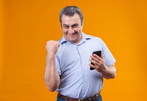 Szczęśliwy mężczyzna w średnim wieku w niebieskiej koszuli w pionowe paski i podnoszący rękę w geście zaciśniętej pięści