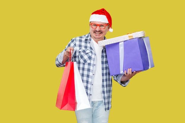 Szczęśliwy mężczyzna w średnim wieku w stylu casual i czerwona czapka nowego roku santa, stojąc i trzymając paczki na zakupy i pudełka na prezenty z uśmiechem toothy, patrząc na kamery. studio strzał, odizolowane na żółtym tle