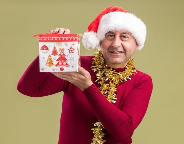 Szczęśliwy mężczyzna w średnim wieku w świątecznej czapce mikołaja z blichtrem na szyi trzymający prezent świąteczny patrząc na kamerę uśmiechnięty wesoło stojąc na zielonym tle