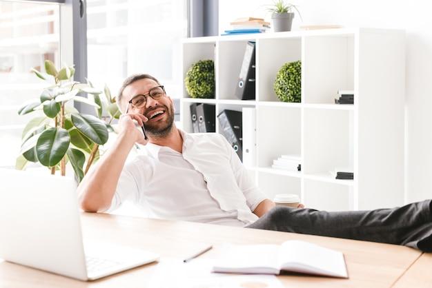Szczęśliwy mężczyzna w wizytowym i okularach rozmawia na czarnym smartfonie podczas picia kawy na wynos w biurze